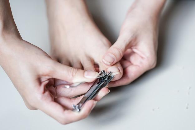 若い女性足の爪を切断