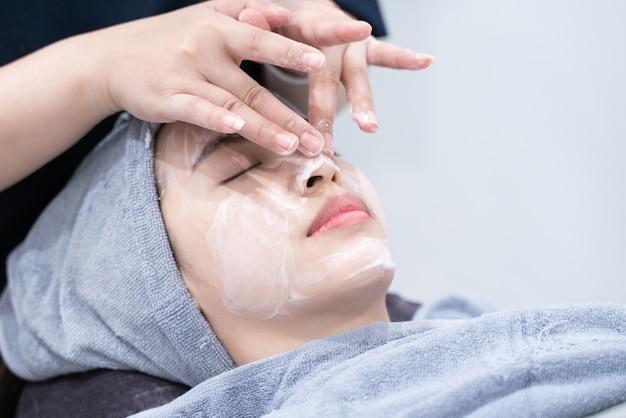 美容院またはクリニックで顔の皮膚を清掃するアジアの女性