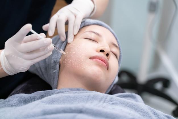 美容クリニックでのニードルメソセラピー。化粧品は女性の顔に注入されます。