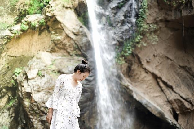 滝と山を持つ女性