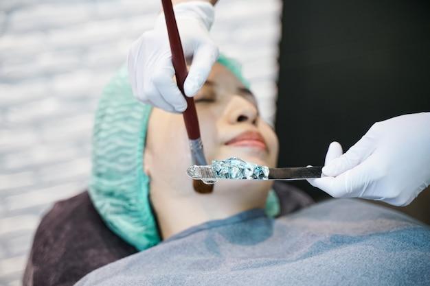 医師は、女性の顔にハイドロジェルマスクを適用します。レーザー治療を受ける若い女性の前に。