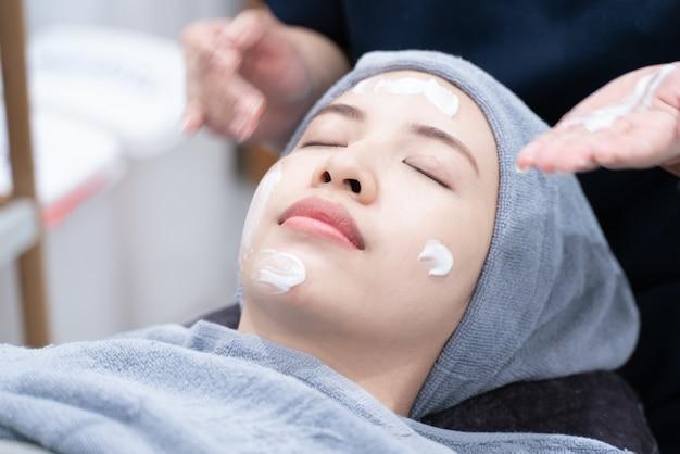ビューティーサロンやクリニックで顔の皮膚のアジアの女性の清掃