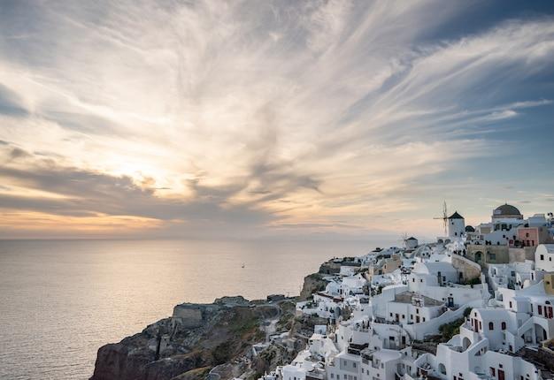 美しい夕日。サントリーニ島、イア。ギリシャ。太陽と雲と夕焼け空