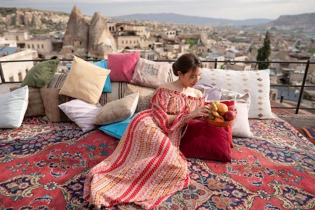 トルコ、カッパドキアのギョレメ市のパノラマを楽しんでいる洞窟の家の屋上で幸せな女性。
