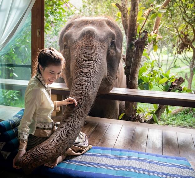 美しいアジアの女性は木製のバルコニーに座って象を養います。