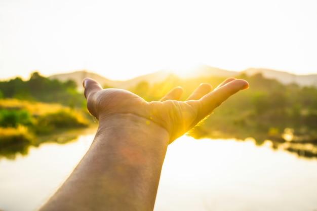 午前中に太陽の光に触れるために手を使用して、手で太陽を拾う