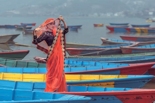 ボート、ネパール、ポカラ市、ペワ湖の上に立っているサリーの女性