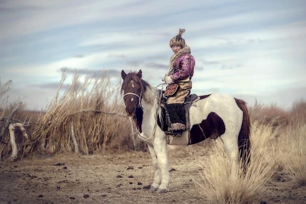 アルタイ山のモンゴルの典型的なモンゴルフォックスドレス文化を伝統的に身に着けているモンゴルワシハンター