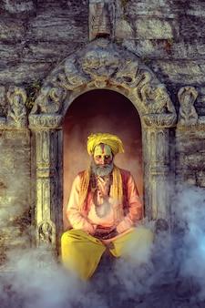 ヨギは、ネパール、カトマンズのパシュパティナート寺院で平和的に瞑想しています。