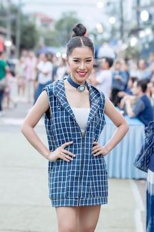 タイのサコナコンの田舎の小さな通りでリラックスし、インディゴのネクタイ染め布ショールをポーズ美しいタイの女の子