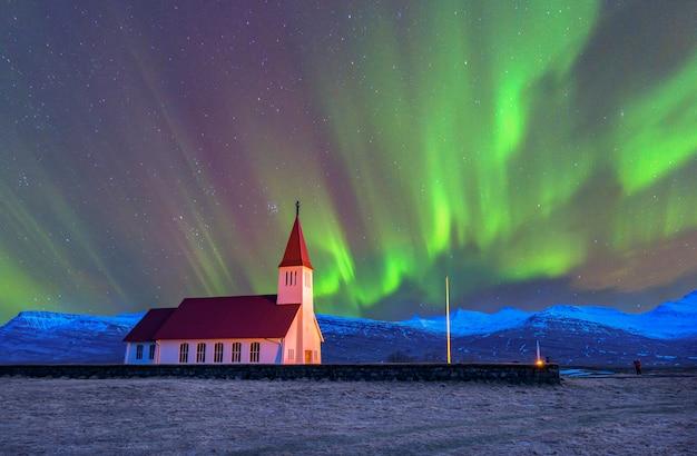 アイスランド南部のヴィック村の教会の上で踊る美しいオーロラ。