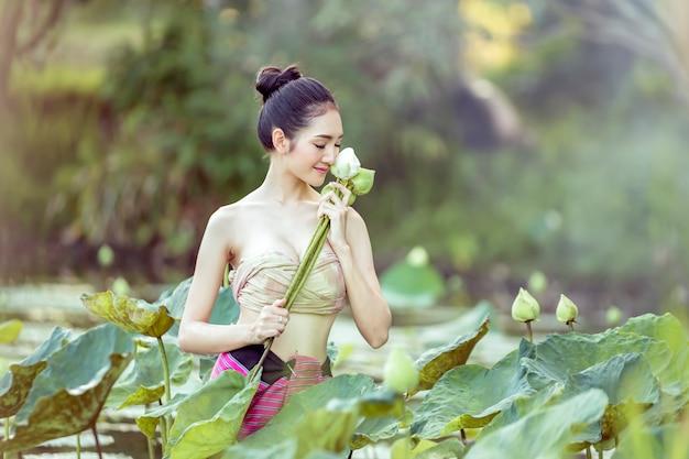 庭でロータスを選ぶ美しいアジアの女性