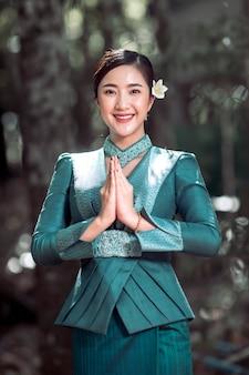 ラオスの伝統的な衣装を着た美しい女性の肖像画は、手を挙げて敬意を払います。これはラオスの美しいシンボルです。