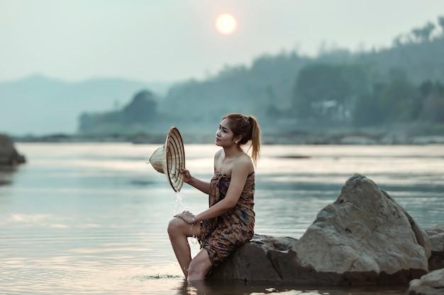 Сельские женщины играя в воде меконга на сумраке, границе таиланда.