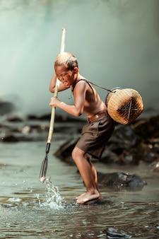 Мальчик ловит рыбу в ручье возле своего дома. в сельской местности таиланда