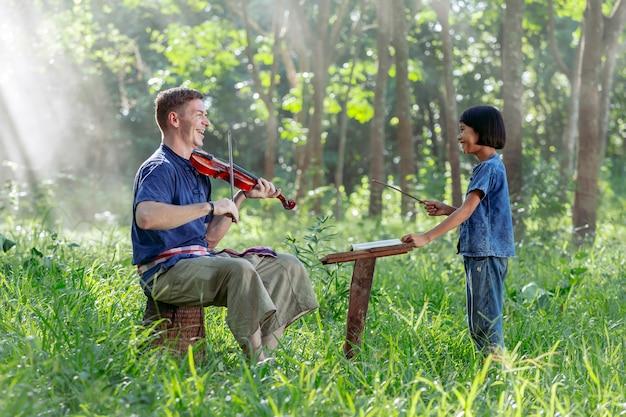 タイの女の子とバイオリンを弾く西洋人