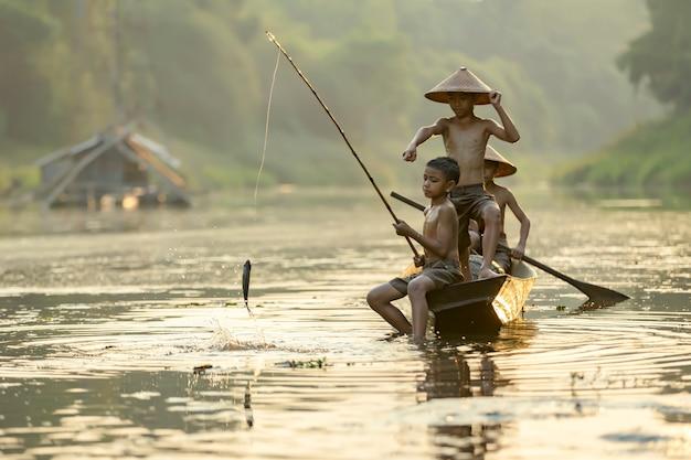 タイの農村部の少年釣り船に座って楽しんで