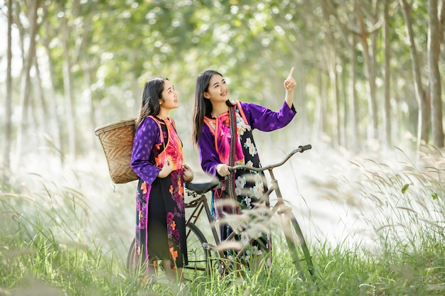 Азиатская женщина ведет велосипед на прогулку по каучуковой плантации