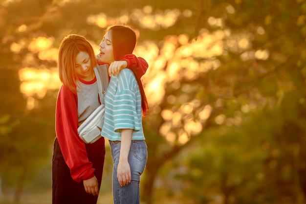 Две молодые счастливые тайские подруги, стоя в саду на закате, сакон накхон, таиланд