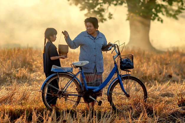 Бабушка собирается забрать свою племянницу. езда на велосипеде в храм, чтобы сделать заслуги в соответствии с буддийскими традициями.