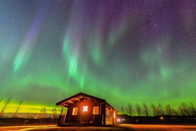 アイスランドの小屋の上の美しい緑と赤のオーロラ