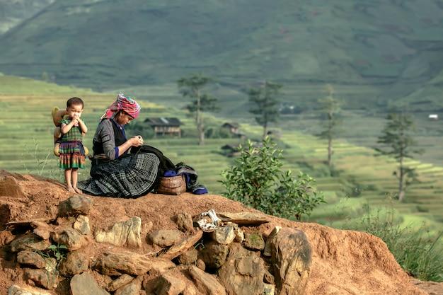 Два коренного вьетнамца, мать и ребенок, шьют утреннюю одежду перед хижиной.