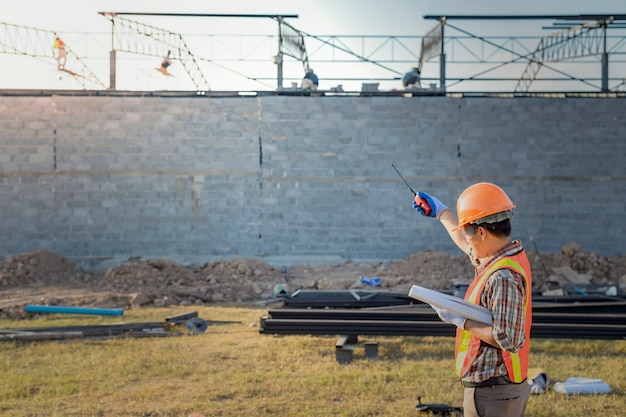 Супервайзер приказывает рабочим завершить строительство в соответствии с планом.