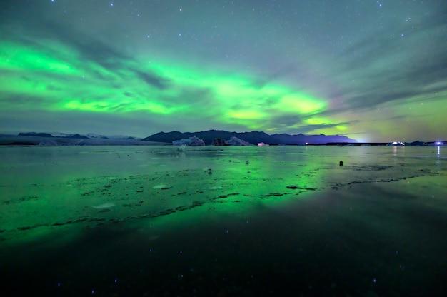 アイスランドの手配ラグーンで踊る美しい緑と赤のオーロラ