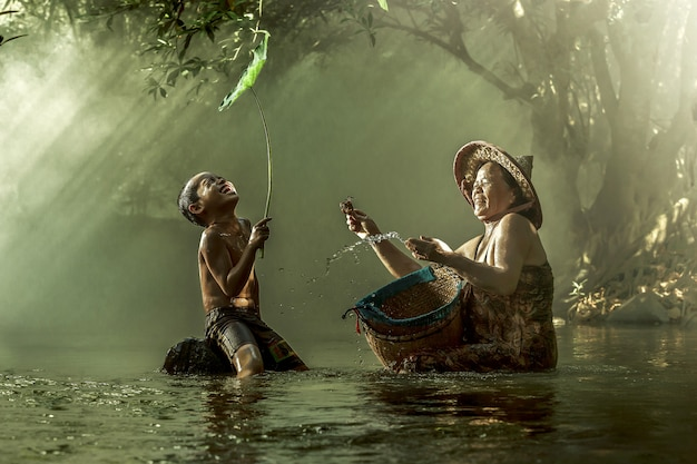 Мать и сын, улыбаясь в потоке.