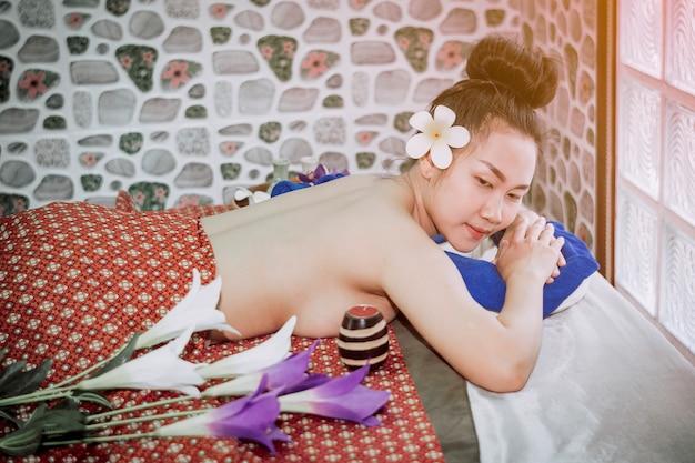 Женщина в положении лежа готовится к спа-массажу