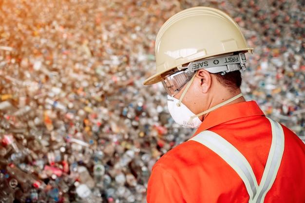 Чиновники, которые одеваются плотно и соответствуют рабочим стандартам. проверка больших отходов для сортировки перед переработкой.