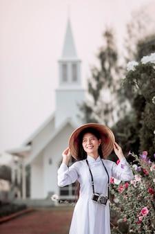 Азиатская женщина в традиционных национальных костюмах во вьетнаме стоит позирует фотографированию христианской церкви