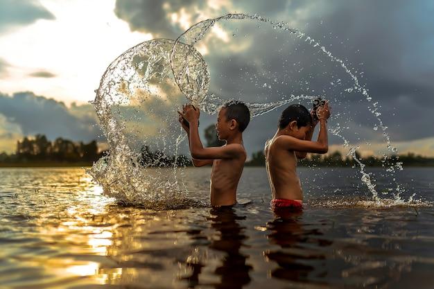 タイの男の子は川にふける