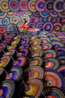 傘職人がビルマの伝統的な傘を作っています。ミャンマー(ビルマ)のバガンのストリートマーケットでカラフルな傘。ビルマ傘