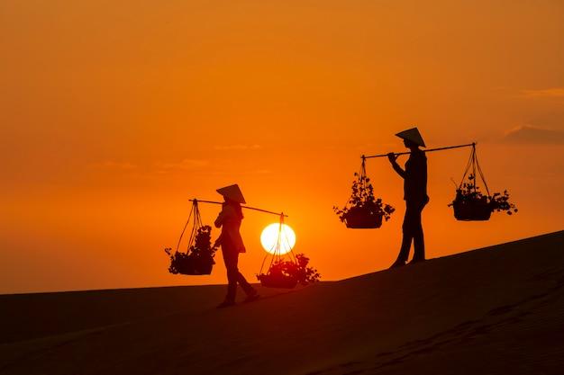 Силуэт торговца лоточниками, путешествующего по пустыне муйне во вьетнаме