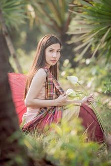 伝統的なタイのドレスを着た美しい少女が座っています。家の近くのプールでハスを集めた後