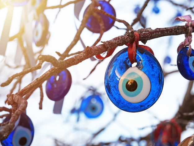 Злые глаза турецкий знаменитый амулет и украшения, висящие на ветках с солнечным светом