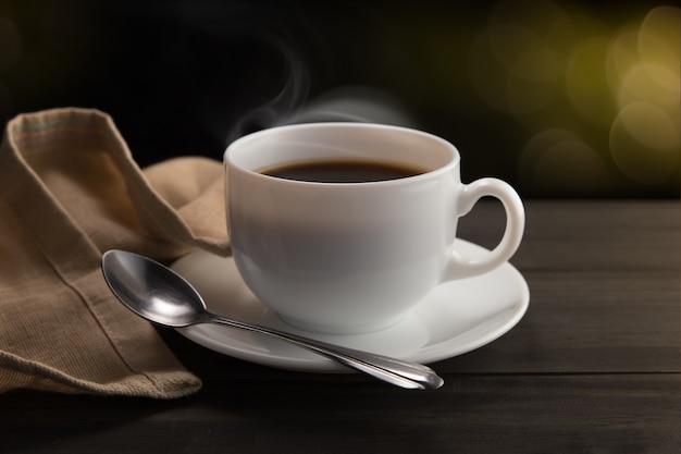 Белая чашка кофе с дымом на черном фоне