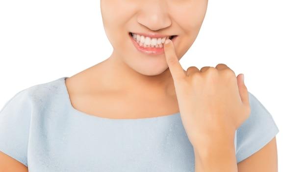 Женщина смотрит в зеркало и проверяет зубы