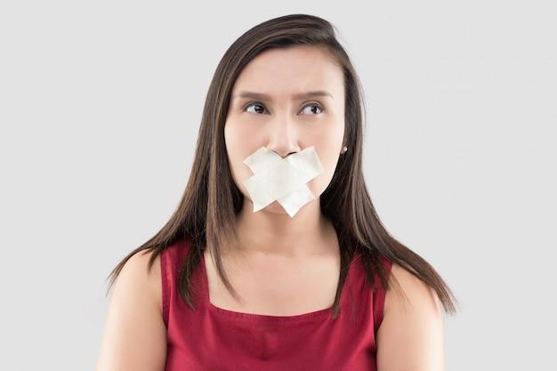 赤いドレスを着たアジアの女性はマスキングテープを使って口を閉じます