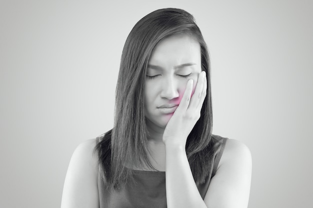 歯痛で苦しんでいる、アジアの女性が苦しんでいる赤いシャツを着て