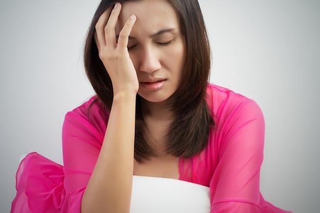 アジアの女性、ベッドで頭痛を持つ、不眠症に苦しんで