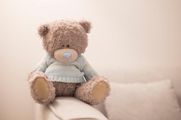 Одинокий плюшевый мишка на коричневом диване.