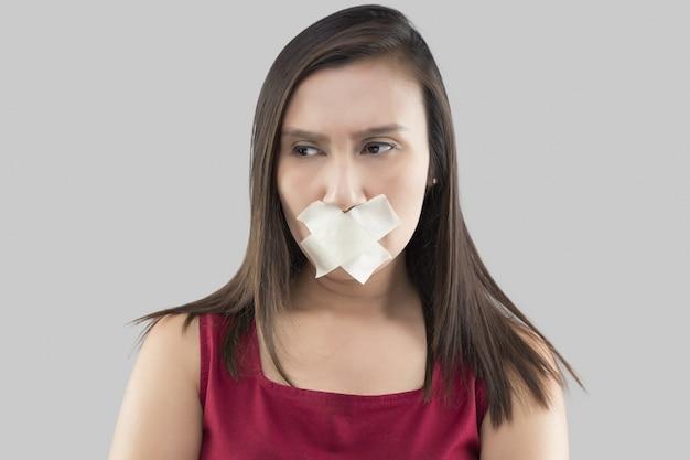 赤いドレスを着たアジアの女性は、灰色についてコメントしたくないため、マスキングテープを使用して口を閉じます