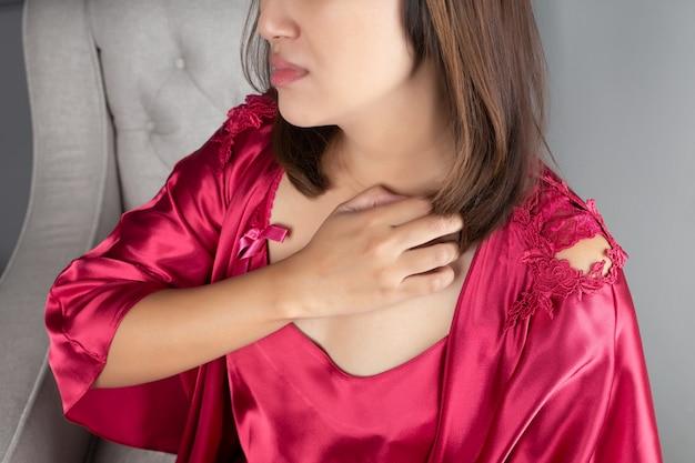 赤いナイトウェアを身に着けているアジアの女性は、かゆみで胸を掻いています。