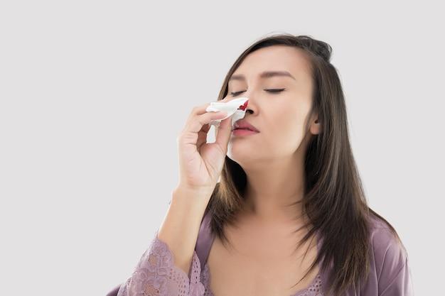 Азиатские женщины в атласной ночной рубашке с кровотечением из носа на сером фоне.