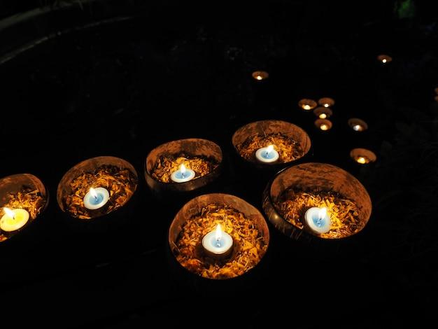 Свеча в скорлупе кокоса с лепестками календулы, чтобы уважать шиву