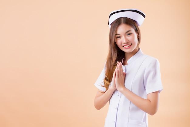 アジアのタイの居心地の良いジェスチャーを行うフレンドリーな笑顔の看護師