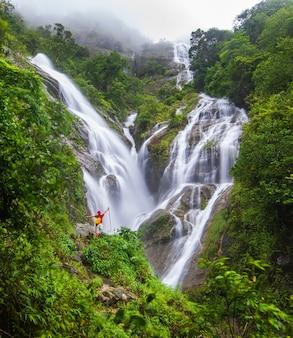 滝の近くのハイキングの若い男