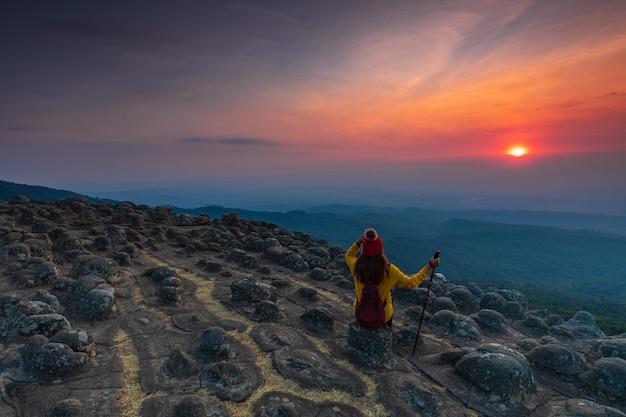 Молодая женщина сидит на скале в горах